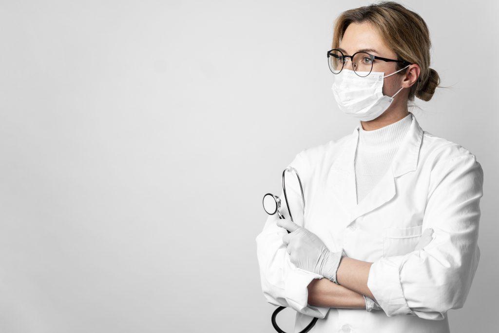 Жена лекар с маска и слушалки замислено гледа на страни през очилата си