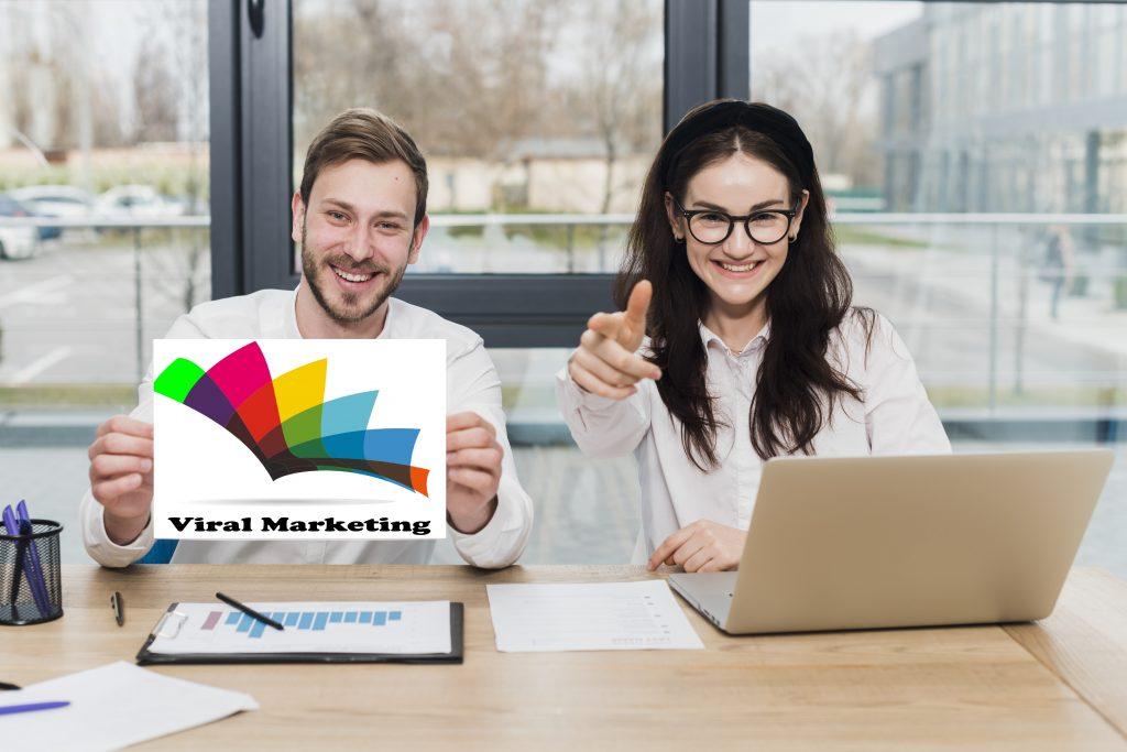позитивни младежи в офис държащи логото на Viral Marketing